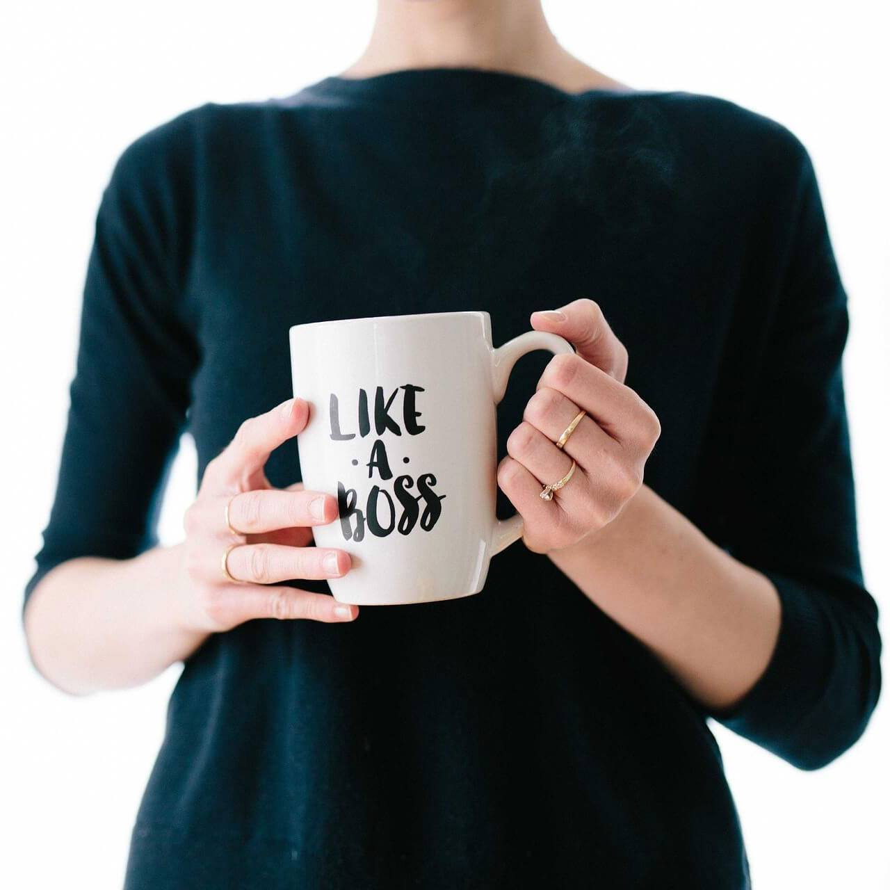 woman in black dress holding boss coffee mug
